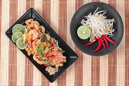 bean sprouts: Thai fried macaroni with shrimp , call Pad Thai Macaroni in Thai, is interfood by using macaroni to cooked with Pad Thai as tamarind sauce,egg,minced roasted nut,green lemon,red hot chili pepper,bean sprouts,lentils,tofu and coriander.  Stock Photo
