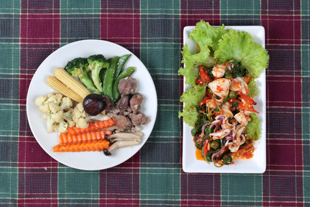 gizzard: Fried mixed vegetable with chicken hearts-gizzard-liver ,as corn,carrot,peas,cauliflower,block kerry,himeji mushroom and shiitake served with fried spicy mixed herb  with squid and lettuce are Thai cuisine  Stock Photo