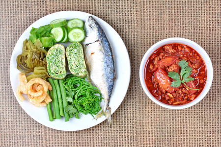 Spicy meat and tomato dip,Nam Prik Ong in Thai,Northern style chili and tomato dip ,with side dish as fired mackarels,winged bean,cha,rolled cha omelet,pork rind,pickle lettuce and cucumber.