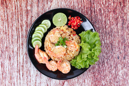 cilantro: Fried rice with shrimp call Khao Pad Kong in Thai is popular asia food s with  halved green lemon,sliced cucumber and lettuce.