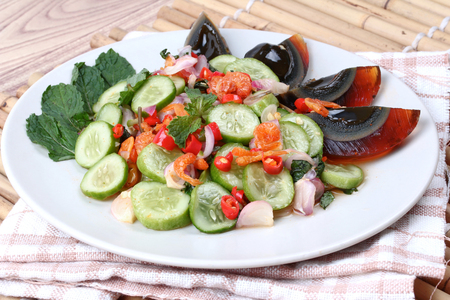 Spicy cucumber salad with dried shrimp and  preserved egg is popular Thai food. Stock Photo