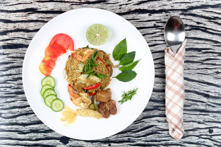 higado de pollo: Thai food ,Fried jasmine rice in green curry with meat (shrimp,squid,chicken liver and chicken hearts) topped halve green lemon,sliced tomato,cucumber,correspondents and basil leaf.