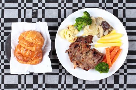 Home made ,Pork steak with sliced carrot, mushroom,corn and croissants .