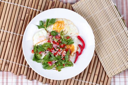 doa: Spicy wing bean with minced pork topped fried egg as Yum Khai Doa in Thai Stock Photo