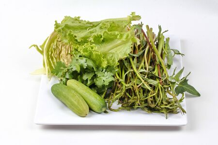 Ready mixed vegetable side dish served  for Thai spicy sour cuisine as cucumber,morning glory,coriander,lettuce and cabbage ,on white background. Stock Photo