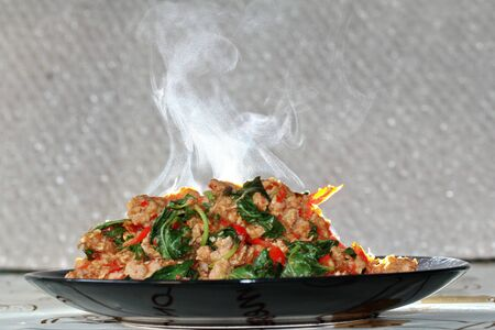 Aroma smell of  of fried spicy basil with minced pork topped  lettuce is top ten of popular Thai food.