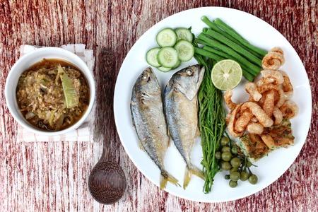 Thai food , Green chili dip as Nam Prik Num in Thai with side dish of deep fired mackarels ,vegetable omelet ,crispy pork rind ,pickle lettuce ,halve green lemon and boiled eggplant ,lentils ,acacia.