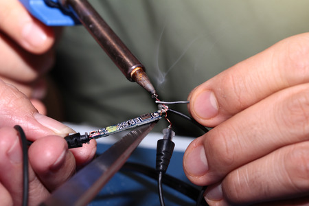 Electronic circuits procedure , Use Soldering Iron to weld connection pore with Tin Wire. Selective focus.