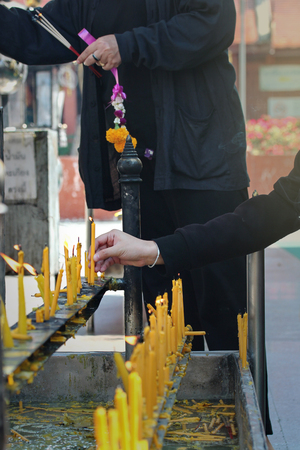 lighted: Buddhists make merit,Placing a lighted candle on the altar of Buddha at temple. Selective focus. Stock Photo