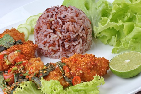 Thai cuisine ,Organic red brown jasmine rice with spicy sour fried chicken salad  call Khao Yum Kai Zap in Thai . Stock Photo