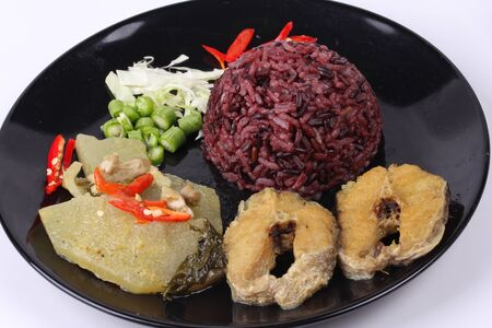 Thai food ready served , Organic red brown jasmine rice topped green chicken curry in coconut milk with fried of striped snakehead fish.