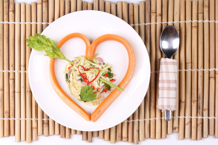 Sausage cheese in heart style with spicy sour green mango salad for Valentine festival Stock Photo