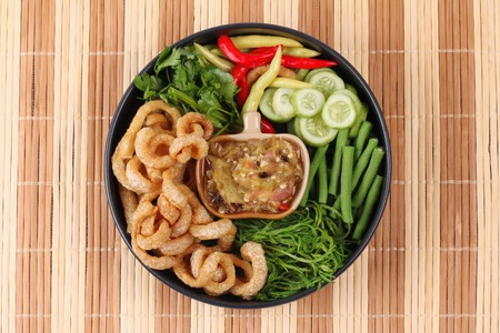 Thai food , Green chili dip as Nam Prik Num in Thai with crispy pork rind ,spicy pepper,boiled cow-pea and sliced cucumber.