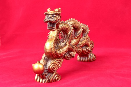 blessings: Golden dragon statue on red background, to celebrate the blessing. According to the beliefs of the in China. To give life and trade flourished. Stock Photo