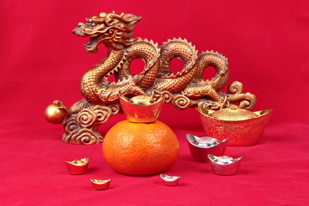 Golden orange with the golden dragon and silver and gold of silver ingots on red background, to celebrate the blessing. According to the beliefs of the in China. To give life and trade flourished.