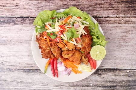 Spicy crispy deep-fried chicken salad with roll green mango call Kai Zap Yum Mamoung in Thai. Stock Photo