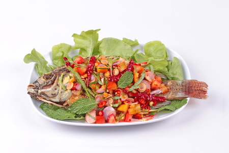 Thai cuisine, Spicy and sour herb salad of fried Tilapia with baby tamarind leaves served isolated on white background.