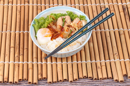 sesame street: Japanese cuisine , Rice with soft boil eggs and fried pork topped white sesame and slicrd dried mackarel in Japanese style call as Oyakodon served on bamboo and wood.