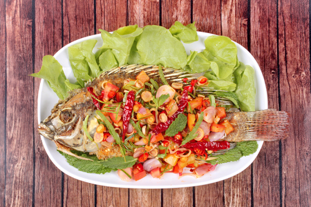 Thai cuisine, Spicy and sour herb salad of fried Tilapia with baby tamarind leaves served on wood.