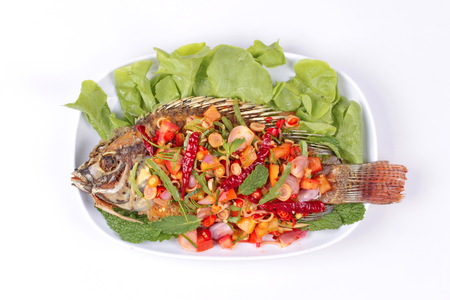 Thai cuisine, Spicy and sour herb salad of fried Tilapia with baby tamarind leaves isolated on white background. Stock Photo