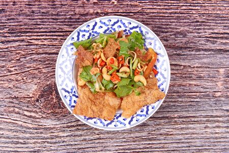 Thai cuisine, Spicy and sour mixed vegetable salad with crispy pork served ,call Pla Moo Phan in Thai. Stock Photo
