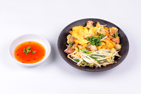 Thai food, Fried oyster omelet with bean sprouts,halve green lemon and shallot call Hoi Tod Khai in Thai served with chili sauce  isolated on white background. Stock Photo