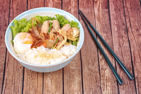 sesame street: Japanese cuisine , Rice with soft boil eggs and fried pork topped white sesame and slicrd dried mackarel in Japanese style call as Oyakodon served on wood. Stock Photo