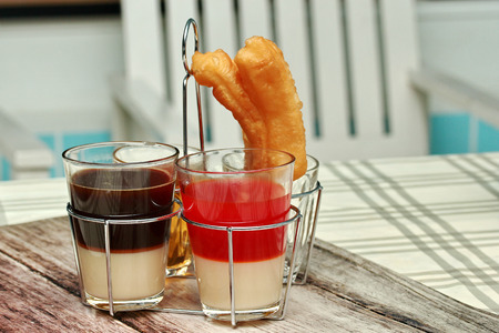 mined: Thai Traditional milk coffee and milk tea served with tea and  Patongko (deep-fried dough stick) in the morning .