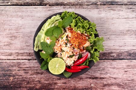 Thai recipe ,Spicy sour crab salad with lettuce ,green lemon and red chili ,call Lab Poo in Thai. Stock Photo