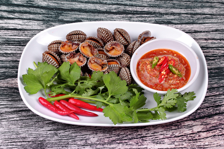 Fresh and delicious soft-boiled blood cockles shell  topped red chili ,coriander and Chinese celery served with spicy sauce  in Korea pattern black dish