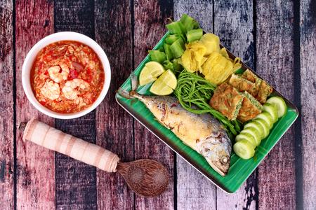 Fresh shrimp chili dip as Nam Prik Kung Sod  in Thai and dish of deep fired mackarels,vegetable omelet,pickle lettuce,halve green lemon,acacia,winged bean and cucumber.