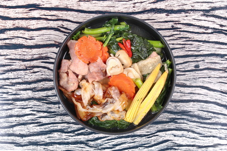 Thai popular food ,Fried big noodle topped Chinese kale and marinated pork in soup with carrot,corn ,mushroom and red chili call Sen Yai Pad Rad Nae in Thai.