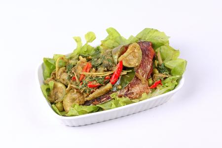 Thai racipe , Fried tilapia fish topped green herb curry in coconut milk call Pla Nil Kaeng Kaew Hwan in Thai Stock Photo
