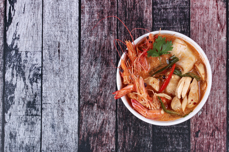 Popular Thai recipe ,Tom Yum fresh prawn with milk and sliced coconut. Thai Spicy and sour prawn soup  call Tom Yum Kung Num Khon in Thai as mixed herb in soup with coconut milk .Have text space on left.