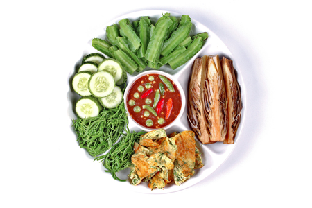 Thai popular food,Spicy shrimp paste dip as Nam Prik Kapi in Thai served with winged bean,vegetable omelet,acacia,banana blossom and sliced cucumber,served on white background.