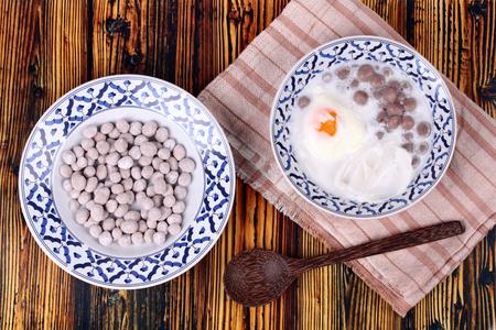 loi: Thai dessert ,Purple potato dumplings with poached egg and coconut roll in sweet coconut cream served in Thai pattern bowl . Call Bua Loi Khai Waan in Thai.