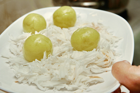 Homemade cooking  Khanom Tom in Thai ,Ball shape of  Doughs wrap the sweet coconut that are boiled and then mixed in soft coconut roll.