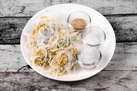 sesame street: Thai popular dessert ,Streamed mung bean topped roll coconut  call Khanom Tau Pab in Thai, served with white sesame and sugar. Stock Photo