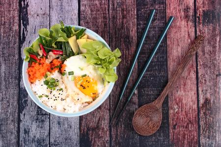 Arroz de jazmín tailandés en estilo japonés, arroz con huevos de hervir suave y pollo frito con cebollino ajo, Oyakodon, en un tazón de fuente japonés.