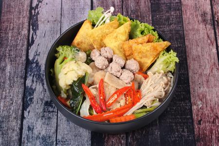Chinese food ,Crisy wonton and meat ball in Chinese kale soup with carrot,corn ,golden needle mushroom,cauliflower,bamboo mushroom and red chili call Kaew Krob Rad Naa in Thai. Stock Photo