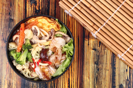 Thai Chinese food,Fried big noodle with omelet topped mixed vegetable in soup as carrot,corn,cauliflower,green oak,broccoli,mushroom and red chili call Sen Yai Pad Rad Nae Kai Jeaw in Thai. No meat. Stock Photo