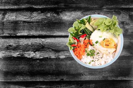 Arroz tailandés de jazmín en estilo japonés, Rice se remata con huevos de ebullición suave y pollo frito con cebollino de ajo, Oyakodon, en tazón de fuente japonés. Tenga un espacio de texto a la izquierda. Foto de archivo