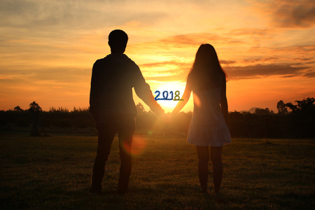 Happy new year 2018 ,Shadow image of couples holding hands with the morning light.Hand in hand together,selective focus with Lens Flare,silhouette