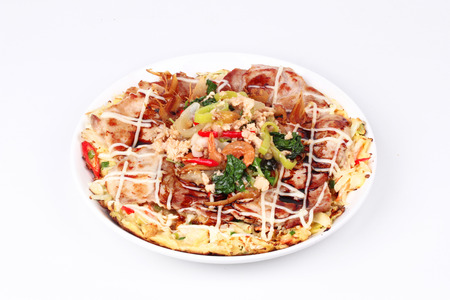 Homemade Japan pizza  (Okonomiyaki)  topped fried spicy basil with minced pork are fried mixed vegetable flour with meat topped sweet sauce ,mayonnaise and topped Thai popular food