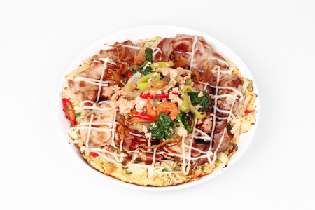 Homemade Japan pizza  (Okonomiyaki)  topped fried spicy basil with minced pork are fried mixed vegetable flour with meat topped sweet sauce ,mayonnaise and topped Thai popular food served on white background.