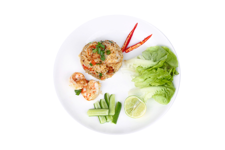Isolated of  Fried rice with shrimp,fresh prawn, topped sliced red hot chili pepper ,sliced cucumber ,halved green lemon and garlic on white plate