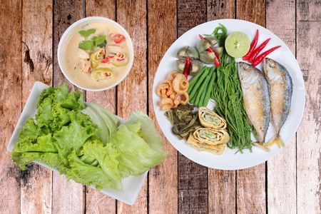Coconut milk and fermented soy bean sauce call Toa Jiaw Loan in Thai and dish of deep fired mackarels,vegetable omelet,crispy pork rind,pickle lettuce,halve green lemon,red chili and boiled of eggplant,lentils,acacia.