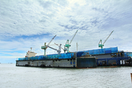 Large commercial ships into floating repair dock. The shipyard crane provide blue mesh  fabric  and drop the buoy oil reservoir. To prevent contamination of the sea.