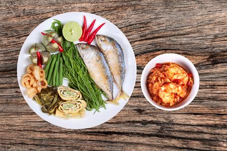Fresh shrimp chili dip as Nam Prik Kung Sod  in Thai and deep fired mackarel,vegetable omelet,crispy pork rind,pickle lettuce,halve green lemon,red chili and boiled of eggplant,lentils and acacia Stock Photo