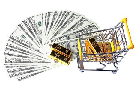 Gold bars 1 kg, in shopping  trolley with yellow mark for supermarket and 2 gold bars on bank note. Stock Photo